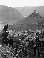 This old castle perched on a hilltop above the Moselle River and the town of Cochem, Germany, is headquarters of the U.S. Fourth Army Corps.  In foreground is Cpl. James C. Sulzer, Fourth Army Corps, Photo Unit.  January 9, 1919.  Sgt. Charles E. Mace. (Army)<br /> NARA FILE #:  111-SC-46155<br /> WAR & CONFLICT BOOK #:  725