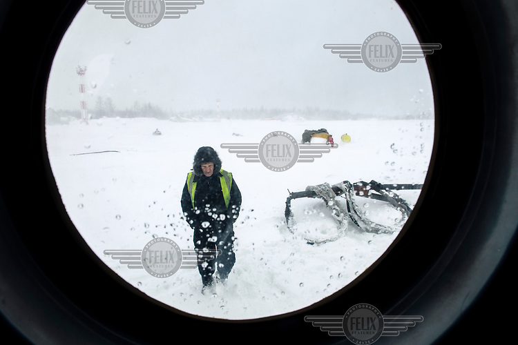A member of the ground crew makes checks before a helicopter takes off from a snow covered airport.
