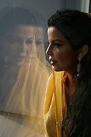 A beautiful young lady gazing through the window in wonder and silent happiness.