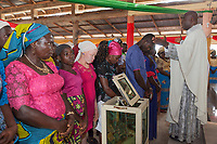 """Nigeria. Abakaliki State. Uburu Amach. St. Patrick's Catholic Church. Igbo men and women during the mass celebration for the 25th Priesthood Anniversary of Reverend Father Edward Inyanwachi (R). An albino woman stands in the first row among other women. Albinism is the """"congenital absence of any pigmentation or coloration in a person resulting in white hair, feathers, scales and skin and pink eyes. The women wear a head tie which is a women's cloth head scarf. The head tie is used as an ornamental head covering or fashion accessory, or for functionality in different settings. Its use or meaning can vary depending on the country and/or religion of those who wear it. The head tie is called gele in Nigeria. 14.07.19 © 2019 Didier Ruef"""