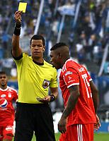 BOGOTA - COLOMBIA - 04 – 03 - 2018: Jhon Alexander Ospina (Izq.), arbitro, muestra tarjeta amarilla a Elkin Blanco (Der.) jugador de America de Cali, durante partido de la fecha 6 entre Millonarios y America de Cali, por la Liga Aguila I 2018, jugado en el estadio Nemesio Camacho El Campin de la ciudad de Bogota. / Jhon Alexander Ospina (L), referee, shows yellow card to Elkin Blanco (R), player of America de Cali during a match of the 6th date between Millonarios and America de Cali, for the Liga Aguila I 2018 played at the Nemesio Camacho El Campin Stadium in Bogota city, Photo: VizzorImage / Luis Ramirez / Staff.