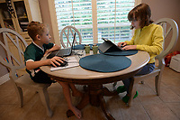 Jackson Presley, 9, (left) and his sister, Katie Presley, 11, use laptop and tablet computers Thursday, Sept. 10, 2020, while completing school work at the dining room table in their home in Springdale. Both are enrolled in the Springdale School District's Virtual Innovation Academy in the Don Tyson School of Innovation. Visit nwaonline.com/200913Daily/ for today's photo gallery. <br /> (NWA Democrat-Gazette/Andy Shupe)
