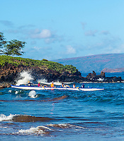 A group of visitors on a tour paddle an outrigger canoe out to sea off Wailea Beach on Maui.