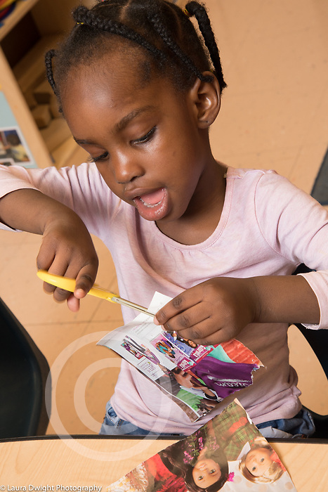 Eucation Preschool 3 year olds girl sitting and using scissors to cut magazine page