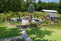 Country garden with barn, swimming pool fenced, water garden, lawn grass, blue skies in summer sunny day