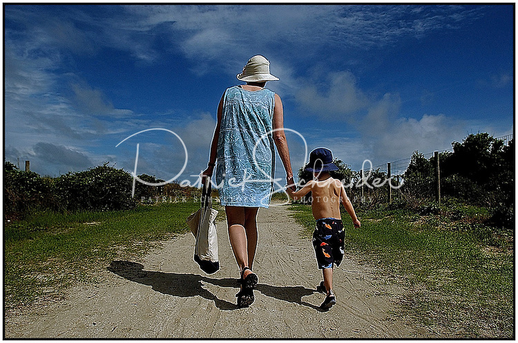 A grandmother walks her grandson along a sandy path to a South Carolina beach. Photo taken on Sullivan's Island near Charleston, SC.  Model released image may be used to illustrate other destinations or concepts.