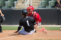 Dante Flores (1) of the Kannapolis Intimidators is tagged out at home plate by Lakewood BlueClaws catcher Austin Bossart (17) at Kannapolis Intimidators Stadium on May 8, 2016 in Kannapolis, North Carolina.  The Intimidators defeated the BlueClaws 3-2.  (Brian Westerholt/Four Seam Images)