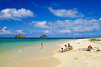 The beautiful Moku Lua islands stand majestic in the warm, blue waters as a family enjoys an afternoon on Lanikai Beach. Located on Oahu's windward side.