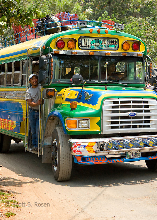 """Guatemalan man looks for passengers for his painted  """"Chicken Bus;"""" an newly painted second hand school bus, near Lake Atitlan, Guatemala"""