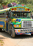 "Guatemalan man looks for passengers for his painted  ""Chicken Bus;"" an newly painted second hand school bus, near Lake Atitlan, Guatemala"
