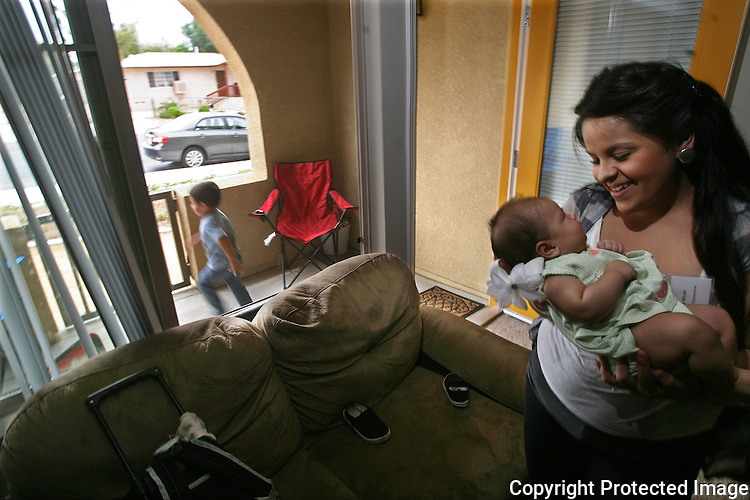 Pottery Court in Lake Elsinore, California, resident Essie Inclan with her 2 month-old daughter Jackelyn in her affordable housing apartment as her son Santiago, 2, runs on the patio outside her apartment. photo for the Californian