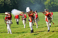 First infantry line of His Majesty's 20th Regiment of Foot fire muskets during a Revolutionary War re-enactment at Fort Ticonderoga, New York, USA.