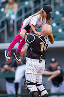 Isabella Elmore (left) is lifted in the air by her father, Phillip Elmore, Gunner's Mate 1st Class in the U.S. Navy, as he surprised her by dressing as a catcher to catch her ceremonial first pitch prior to the International League baseball game between the Buffalo Bison and the Charlotte Knights at BB&T Ballpark on May 9, 2014 in Charlotte, North Carolina.  Phillip Elmore is currently stationed in Germany, and he planned the surprise trip home to coincide with Isabella's graduation from her communion class.  (Brian Westerholt/Four Seam Images)