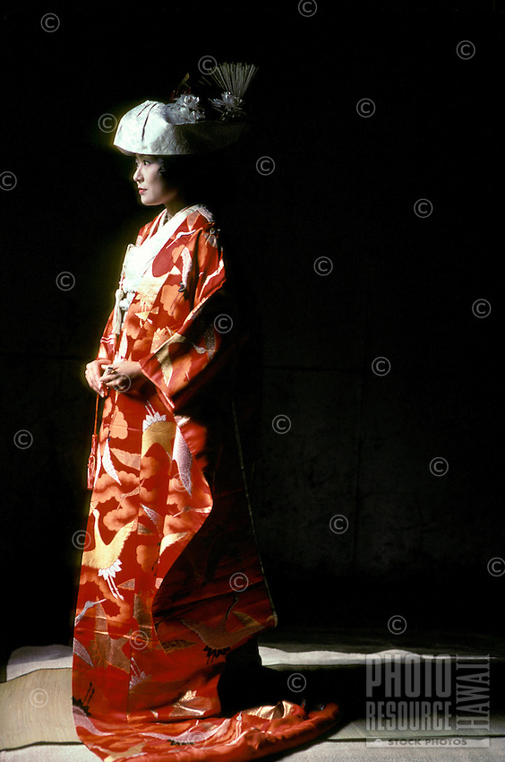 Japanese bride dressed in traditional wedding dress (kimono). The black background and the bride's shadow provide sharp contrast with the bright red and pattern of the kimono and the bride's pale makeup and head dress