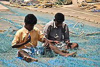 Andaman Islands, India. Two barefoot men in their 30s sitting on the floor fixing a fishing net