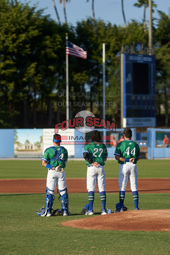 Florida Gulf Coast Eagles catcher Johnny Long (14), pitcher Gus Carter (27) and first baseman Joe Kinker (44)  during the national anthem before an NCAA game against the Miami Hurricanes on March 17, 2021 at Swanson Stadium in Fort Myers, Florida.  (Mike Janes/Four Seam Images)