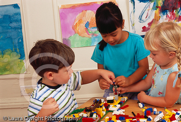 two girls and a boy all 4 years old playing together with legos horizontal joint project