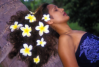 Polynesian woman against palm tree with plumeria in hair.