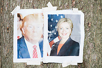 Photos of presidential candidates Donald J. Trump and Hillary Rodham Clinton hang on a tree near a protest camp in the protest area in FDR Park outside of the secure area surrounding the Democratic National Convention at the Wells Fargo Center in Philadelphia, Pennsylvania, on Wed., July 27, 2016.