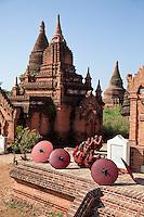 Myanmar, Burma. Bagan.  Young Novice Monks Praying Outside a Temple.