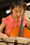 7 year old girl playing musical instrument cello