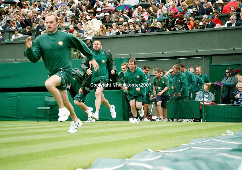 27-6-07,England, Wimbldon, Tennis, RAIN, Court attendants running on center court to put the cover on.