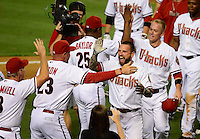 Jun. 8, 2012; Phoenix, AZ, USA; Arizona Diamondbacks third baseman Ryan Roberts (center) is congratulated by manager Kirk Gibson after hitting a three run walk off home run in the ninth inning against the Oakland Athletics at Chase Field.  Mandatory Credit: Mark J. Rebilas-