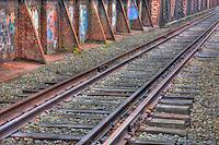 Railroad tracks and graffiti covered deck leading to the historic Free Black Bridge, a through truss pin-connected bridge over the Androscoggin River on the Maine Central Railroad in Brunswick, Maine