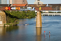 """""""Focus One Point And Breathe"""" with a USA space rocket is a famous and beloved inspirational graffiti painting on a the railroad bridge over Lady Bird Lake, overlooking the Austin skyline."""