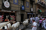 Participants run past Torrestrella's bulls during the fifth bull run of the San Fermin Festival in Pamplona, northern Spain on July 11, 2013. © Pedro ARMESTRE