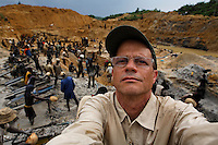 Randy Olson, photographer makes a self portrait while photographing gold mining on river banks outside of Prestea.