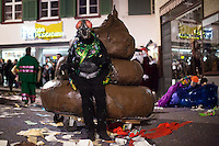 A participant dressed as a fly stands next to a large model of a pile of poop moments before the official end of Fasnacht, the Carnival of Basel. Feb. 26, 2015.