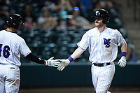 Alex Destino (23) of the Winston-Salem Dash slaps hands with teammate Luis Curbelo (16) after hitting a 2-run home run during the game against the Hickory Crawdads at Truist Stadium on July 10, 2021 in Winston-Salem, North Carolina. (Brian Westerholt/Four Seam Images)
