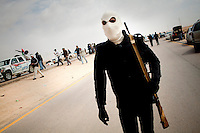 A man holding a gun wears a mask over his face as he joins the front at Ajdabiya. On 17 February 2011 Libya saw the beginnings of a revolution against the 41 year regime of Col Muammar Gaddafi.