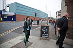 Tranmere Rovers 0 Stoke City 2, 25/09/2013. Prenton Park, Captial One Cup Third Round. A home team's supporter pausing for a cigarette at Prenton Park next to a sign advertising the Manchester United versus Liverpool match taking place the same night before Tranmere Rovers host Stoke City in a Capital One Cup third round match. The Capital One cup was formerly known as the League Cup and was competed for by all 92 English Premier League and Football League clubs. Visitors Stoke City won the match 2-0, watched by a crowd of 5,559 spectators. Photo by Colin McPherson.