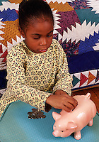 An African-American child saves money in her piggy bank.