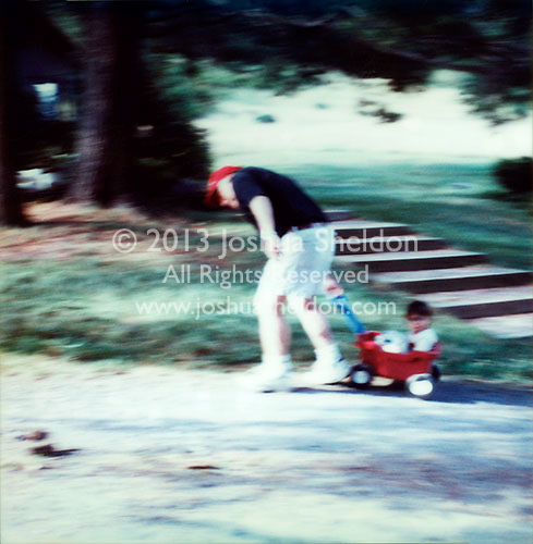 Father pulling boy in toy wagon<br />