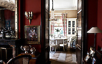 A view into the dining room from the red warmth of the adjacent study
