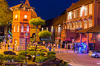 Stadthuys on right at night, Former Dutch Governor's Residence and Town Hall, Built 1650.  Illuminated Trishaw in lower right, waiting for tourists.  Melaka, Malaysia.
