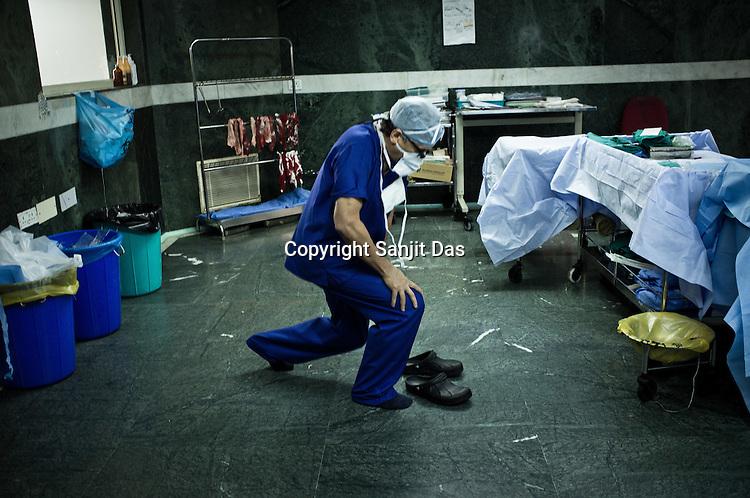 58 year old heart surgeon, Dr. Devi Prasad Shetty stretches after an operation at the Narayana Hrudayalaya in Bangalore, Karnataka, India. Photo: Sanjit Das/Panos