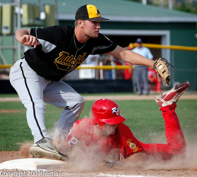 RAPID CITY, SD -- AUGUST 2, 2009 -- Parker Sullivan of Rapid City Post 22 is forced out at first after a line drive was caught during their game with Mitchell at the 2009 South Dakota State American Legion Baseball Tournament at Floyd Fitzgerald Stadium Sunday. Covering first is Jordan Piper. (Photo by Dick Carlson/Inertia)