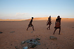 Two Himba women and a girl begin walking out into the desert, away from the remains of a campfire. Himba are nomadic herders of goats and cattle, living in the dry regions of northwestern Namibia and southern Angola. [NO MODEL RELEASE]