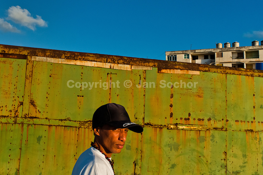 """A young Cuban man, wearing a baseball cap, walks in front of a rusty container in Alamar, a public housing complex in the Eastern Havana, Cuba, 9 February 2009. The Cuban economic transformation (after the revolution in 1959) has changed the housing status in Cuba from a consumer commodity into a social right. In 1970s, to overcome the serious housing shortage, the Cuban state took over the Soviet Union concept of social housing. Using prefabricated panel factories, donated to Cuba by Soviets, huge public housing complexes have risen in the outskirts of Cuban towns. Although these mass housing settlements provided habitation to many families, they often lack infrastructure, culture, shops, services and well-maintained public spaces. Many local residents have no feeling of belonging and inspite of living on a tropical island, they claim to be """"living in Siberia""""."""