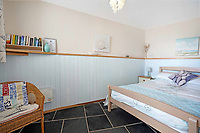 BNPS.co.uk (01202) 558833.<br /> Pic: MarchandPetit/BNPS<br /> <br /> Pictured: A bedroom.<br /> <br /> A cute cottage cut into the cliffside with spectacular views along a three-mile stretch of beach is on the market for £500,000.<br /> <br /> Unlike most coastal properties in the area, Boathouse Cottage does not look out to sea but along the popular beach.<br /> <br /> The quirky holiday home is in the picturesque village of Torcross, Devon, right next to Slapton Sands.