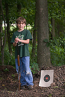 Young boy poses with bb gun and target after his first lesson in gun safety and shooting technique