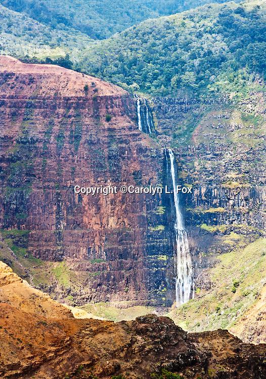 A waterfall rushes down the mountain in Waimea Canyon on Kauai, Hawaii.
