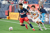 FOXBOROUGH, MA - MAY 22: Brandon Bye #15 of New England Revolution turns to pass the ball away from Caden Clark #37 of New York Red Bulls during a game between New York Red Bulls and New England Revolution at Gillette Stadium on May 22, 2021 in Foxborough, Massachusetts.