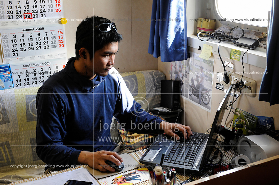 GERMANY Hamburg, Filipino seaman in his cabin on cargo vessel MV Merwedijk in harbour , skyping with family at home in the Philipinnes/ DEUTSCHLAND Hamburg , philippinischer seeman auf  einem Schiff im Hafen, Kommunikation mit Familie per internet