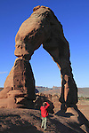 Man photographing his girl friend, Delicate Arch, Arches National Park, Moab, Utah,