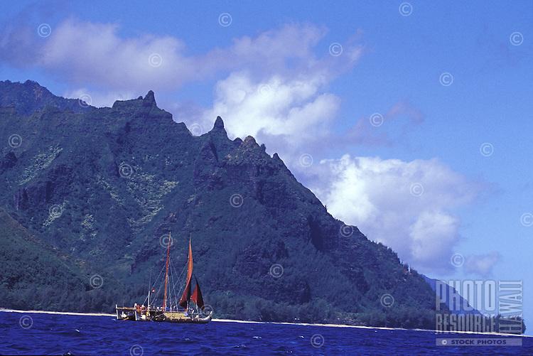 Hokulea, a traditional double hulled Hawaiian sailing canoe, sets sail off the Na Pali Coast for the voyage to the Northwestern Hawaiian Islands